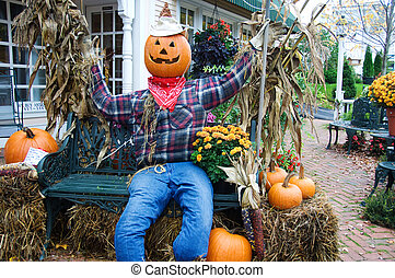 Pumpkin head - Scarecrow with a pumpkin head, sitting on a...