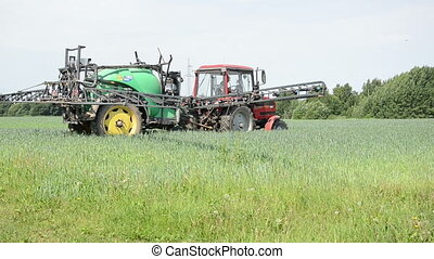 tractor work spray - worker spreads tractor sprayer makes...