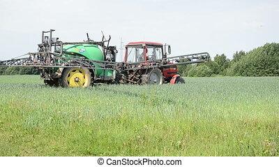 tractor work spray - worker spreads tractor sprayer makes...