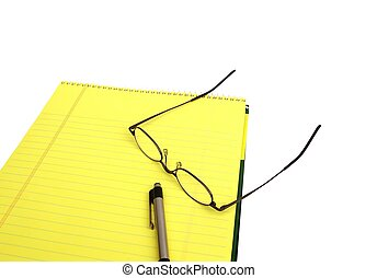 Notepad - Yellow notepad with pen and reading glasses on a...