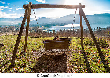 Woman sitting on a large swing with view in klagenfurt am...
