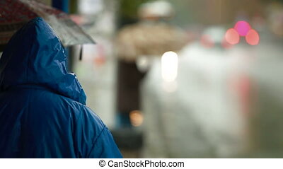 People waiting at bus stop under rain