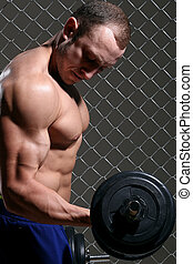 Strong, muscular man with a dumbbell