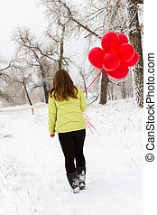 Valentines Day - Teenager girl with red balloons walking in...
