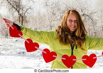 Valentines Day - Teenager girl holding string of red hearts.