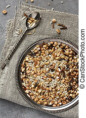 Uncooked multigrain rice in metal plate on wooden background
