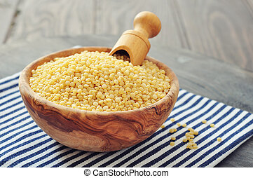 Raw couscous in wooden bowl on wooden background closeup