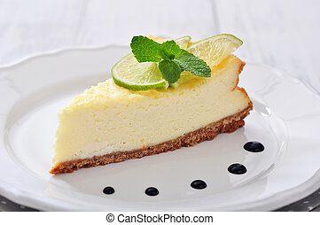 Cheesecake with lime and mint on plate closeup