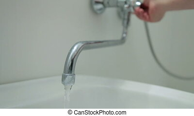 Hand opening water tap in the bathroom