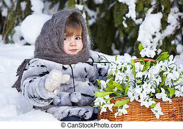 Little girl in a winter wood with the big basket of...