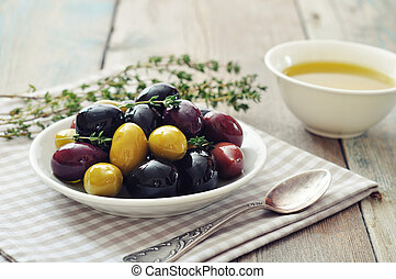 Different kinds of olives on plate with olive oil on wooden...