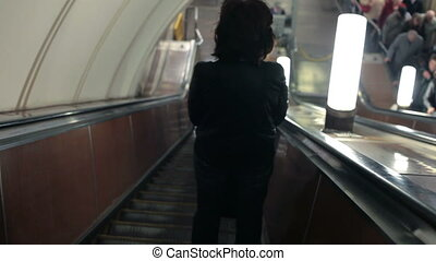 People going down the subway escalator