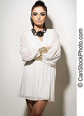 Vogue. Beautiful woman posing in white dress