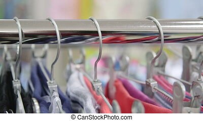 Clothing hanging on hangers at clothes shop