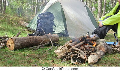 Campfire at campground - Woman sits near campfire at the...
