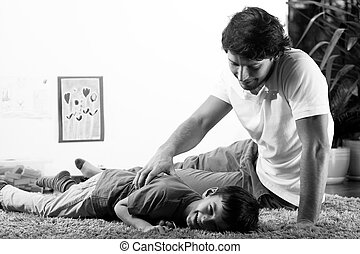 Happy dad tickling son - Happy young father tickling his...