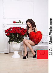 Valentine's Day. Beautiful sexy woman with gift red heart and bouquet of roses