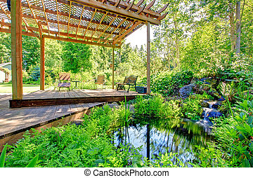 Picturesque backyard farm garden with small pond and patio...