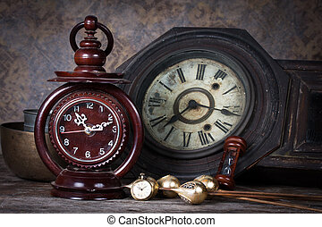 Group of objects on wood table. old clock, hourglass,...