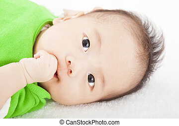 Baby having sucking finger and lying on the towel