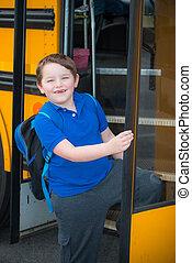 Happy child boarding school bus
