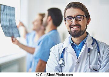 Young clinician - Portrait of friendly doctor looking at...