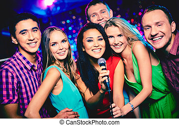 Karaoke party - Portrait of happy girls and guys singing in...
