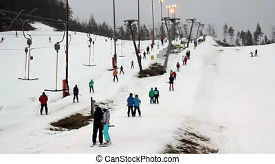 A view of a ski resort with lots of people are pulled by the...