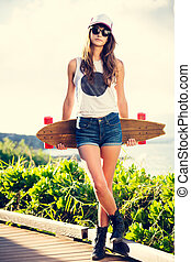Beautiful young woman with a skateboard - Fashion lifestyle,...