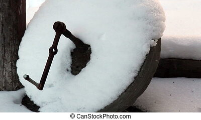 A circular wooden object with snow