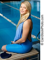 Young blond woman in swimming suit sitting on a bench near pool