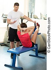 Personal fitness trainer explains to a young woman how to do abdominal exercise