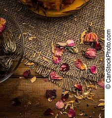 Flower tea petals on sackcloth over wooden background