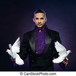 Young handsome brunette magician man in stage costume with...