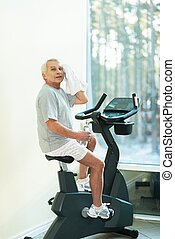 Tired senior man with towel on exercise bike in fitness club