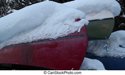 Four boats turned upside down are covered with snow - Four...