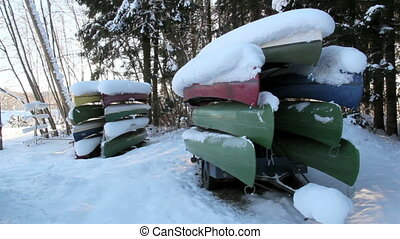 Two sets of boats piled upside down with snow
