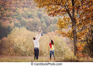 Family relaxing together in golden autumn nature - Happy and...