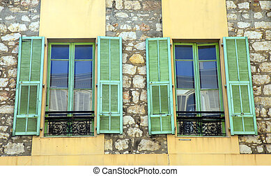 Two french rustic windows with old green shutters in stone...
