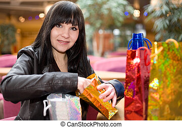 woman with gifts - happy brunette woman in shopping mall