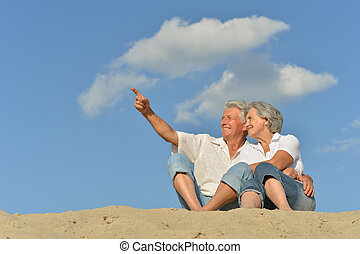 Happy old couple sitting on the sand in the summer