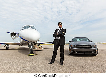 Businessman Standing By Car And Private Jet At Terminal -...