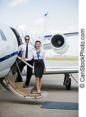 Confident Airhostess And Pilot Standing On Private Jet's...