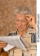 Elderly man reading newspaper on beige background
