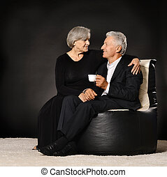 Senior couple drinking tea sitting in black armchair