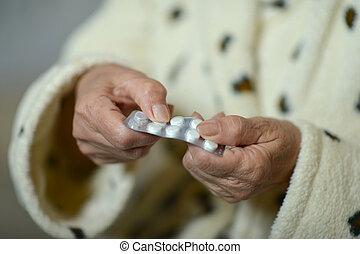 Sick senior woman taking pills
