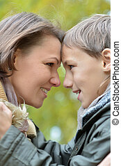 Mother and son on a walk during the fall of the leaves in...
