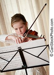 Child playing violin at home - Cute child (little girl)...