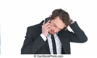 Puzzled businessman talking on a mobile phone scratching his...