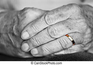 Old hands with wedding band - Close up on elderly woman...